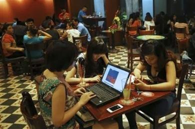 Trong bức ảnh ngày 14.5.2013 này, ba cô gái Việt Nam sử dụng laptop và điện thoại thông minh để lên mạng tại một quán cà phê ở Hà Nội. Các nhà hoạt động dân chủ và blogger Việt Nam đang chiến đấu chống lại một chiến dịch ngăn chặn, hack và do thám mà một đội quân bí mật ủng hộ chính phủ tiến hành trên mạng. Mặc dù họ không thể chứng minh được điều đó, song các nhà hoạt động và chuyên gia phân tích rất nghi ngờ sự dính líu của chính phủ Việt Nam trong chiến dịch, vốn đang kìm hãm phong trào dân chủ ở đất nước này. Ảnh: (AP Photo/Na Son Nguyen, File)