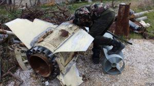 Một chiến binh phe nổi dậy, Quân đội Syria Tự do, ở Latakia, quan sát một vỏ đạn chưa nổ