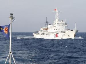 Một tàu hải cảnh Trung Quốc gần giàn khoan, phía trái là cờ của lực lượng tuần duyên Việt Nam. Ảnh chụp ngày 14/05/2014. REUTERS/Nguyen Ha Minh
