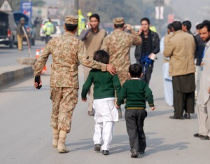A soldier escorts schoolchildren after they were rescued from the Army Public School that is under attack by Taliban gunmen in Peshawar