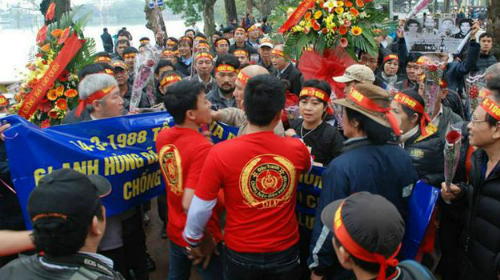 """Nhóm người mặc áo đỏ in chữ """"DLV"""" giăng cờ đỏ búa liềm trước tượng đài, ngăn cản người dân đặt hoa, thắp hương tưởng niệm các liệt sĩ Gạc Ma."""