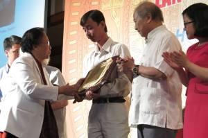 Bà Nguyễn Thị Bình, chủ tịch Quỹ Văn hóa Phan Châu Trinh trao giải cho nhà nghiên cứu Phạm Hoàng Quân. Ảnh: Trâm Anh