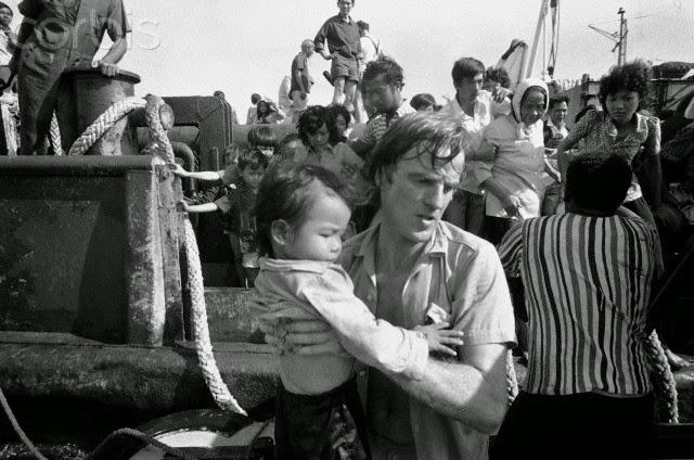 Bác sĩ Bernard Kouchner thuộc tổ chức Không biên giới - Sans Frontieres - mang một đứa trẻ Việt tị nạn từ tàu Hải Hồng lên một bệnh viện trên Tàu l'Ile de Lumiere của Pháp vào năm 1979. Ảnh của Corbis.