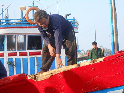 Ngư dân Nguyễn Văn Quang, chủ tàu cá QNg 90205 TS bên vết vỡ của thân tàu do bị tàu Trung Quốc tấn công.