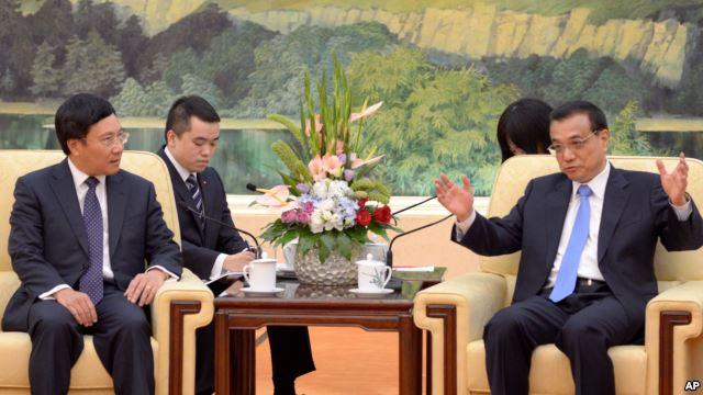 Bộ trưởng Ngoại giao Việt Nam (trái) lắng nghe ông Lý Khắc Cường trong cuộc hội kiến tại Bắc Kinh hôm 18/6.
