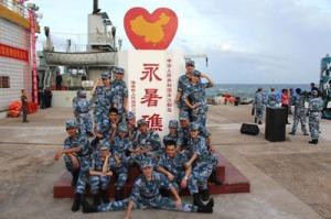 """Một nhóm binh sĩ nam nữ Trung Quốc chụp hình tại bia """"Vĩnh Thử Tiêu"""" tức bãi Đá Thập của Việt Nam. Tấm bia này đã được dựng từ nhiều năm trước. (Hình: sina)"""
