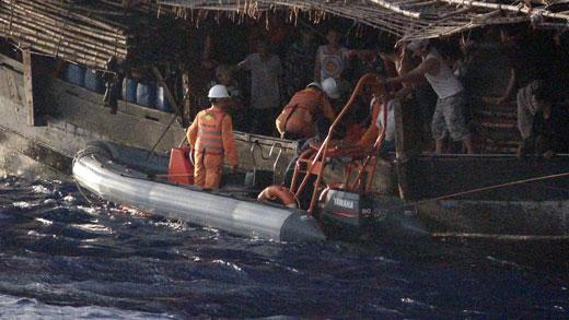 Tiếp cận, đưa ngư dân Phạm Thanh Ngọc vào bờ cấp cứu. Ảnh: Xuân Sơn.