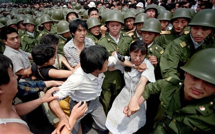 Một nhóm sinh viên, trong đó có 1 cô gái cầm máy ảnh, đang giằng co với quân đội PLA tại Thiên An Môn, 1989 (Ảnh: Internet)