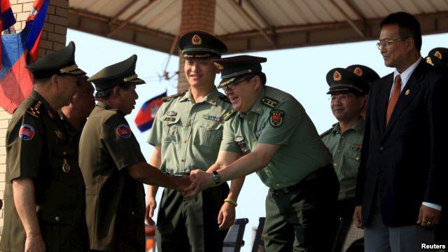 Bộ trưởng Quốc phòng Campuchia Tea Banh (trái) bắt tay với cố vấn quân đội Trung Quốc trong một buổi lễ tốt nghiệp tại Học viện quân đội ở tỉnh Kampong Speu, Campuchia