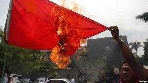 Hành động lấn lướt của Trung Quốc ở biển Đông đã làm bùng ra nhiều cuộc biểu tình bài Bắc Kinh tại các quốc gia cũng có tuyên bố chủ quyền ở biển Đông. Trong ảnh là một người biểu tình Philippines đốt cờ của Trung Quốc.