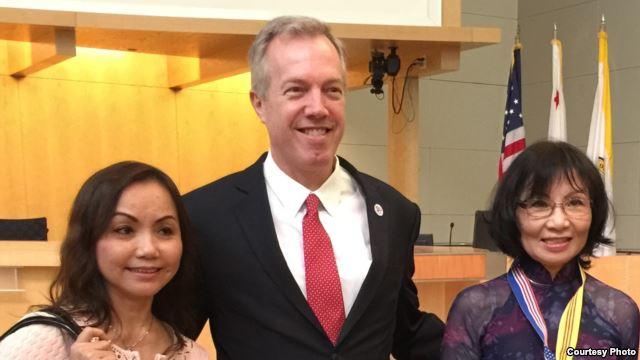 Cô Đỗ Minh Ngọc với dây đeo có cờ vàng chụp hình chung với Đại sứ Ted Osius sau buổi thảo luận (ảnh Bùi Văn Phú)