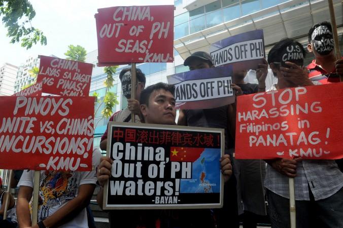 Những người phản đối tổ chức một cuộc biểu tình trước Lãnh sự quán Trung Quốc tại khu tài chính của Manila vào ngày 7 tháng 7, tố cáo chính quyền Trung Quốc xâm lược lãnh thổ trên Biển Đông. Trung Quốc có thể sớm bắt đầu giai đoạn thứ hai trong dự án xây dựng những hòn đảo nhân tạo ở vùng biển tranh chấp. (Jay Directo / AFP / Getty Images)