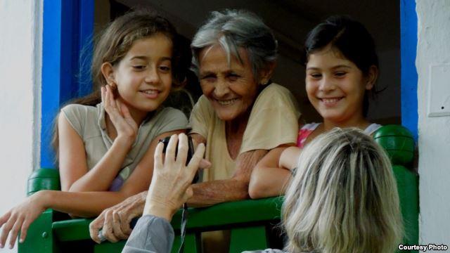 Chủ quán Café de Maria cùng hai người cháu tươi cười xem hình vừa được một du khách chụp (ảnh Bùi Văn Phú)