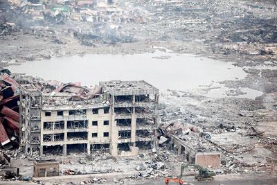 Một tòa nhà bị tàn phá gần hố tròn, trung tâm của vụ nổ, nơi kho hàng của hãng Thụy Hải đã biến mất. (Hình: ChinaFotoPress via Getty Images)