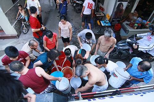 Ảnh: Nam Nguyễn (Chiều 21/8/2015, người dân trong ngõ 814 đường Láng (Đống Đa) chia nhau từng xô nước)