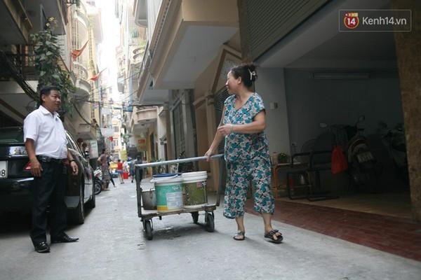 Một phụ nữ hồ hởi khi hứng được nhiều xô nước về nhà mình.