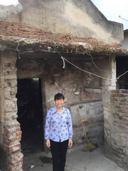 Chị Thêu trước ngôi nhà của mình.