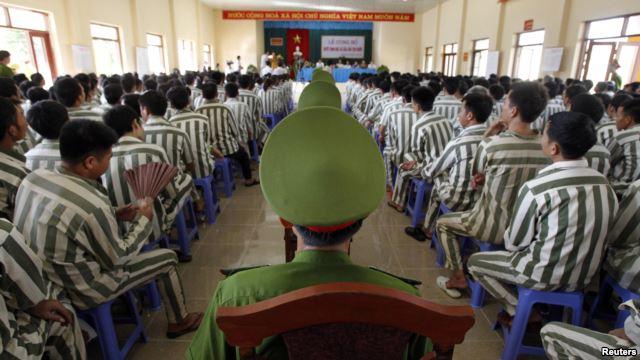 Cảnh sát canh gác trong lúc tù nhân chờ được phóng thích khỏi nhà tù Hoàng Tiến, khoảng 100 km từ Hà Nội. Ảnh: Reuters