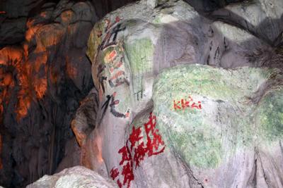 """Nhiều chữ được viết bằng mực hoặc sơn nhưng rất khó tẩy xóa do ở cao hoặc mực, sơn đã """"chết"""" vào đá. (Hình: Báo Lao Động)"""