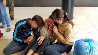 Mẹ, anh trai và chị gái của em Dư đang chờ kết quả khám nghiệm tử thi. Ảnh chụp tại tại sân nhà tang lễ Bệnh viện Bạch Mai (Hà Nội), trưa ngày 11/10/2015. Ảnh: Nguyễn Đình Hà.