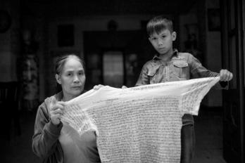 Bà Việt và cháu Kiên, con của anh Mạnh cầm thư viết trên áo của anh Mạnh gửi ra. Nguồn: FB Chau Doan