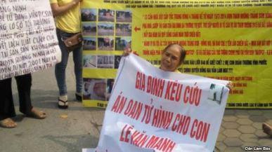 Bà Nguyễn Thị Việt, mẹ của tử tù Lê Văn Mạnh, cầm biểu ngữ kêu cứu cho con. Ảnh: DLB