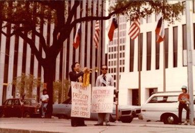 Nhà báo Nguyễn Ðạm Phong (phải) đứng đeo biểu ngữ phản đối Cộng Sản ở Houston, Texas, năm 1979. (Hình: Nguyễn Thanh Tú cung cấp)