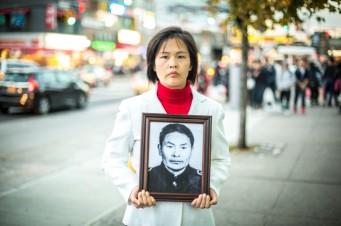 Cô Giang Lý tại Flushing, Queens, ngày 1 tháng 11 năm 2015, trên tay là bức ảnh cha cô, người đã bị ĐCSTQ sát hại chỉ vì tập luyện Pháp Luân Công (Benjamin Chasteen/Epoch Times)