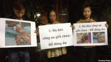 ẹ và anh chị của nạn nhân Đỗ Đăng Dư cầm biểu ngữ phản đối. (Facebook: Dung Truong)