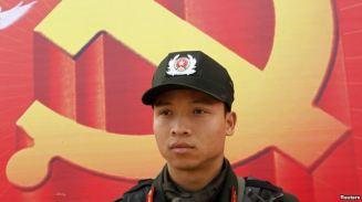 Một cảnh sát đứng phía trước tấm áp phích biểu tượng cộng sản bên ngoài Trung tâm Hội nghị Quốc gia, Hà Nội ngày 15/1/2011. Ảnh: Reuters