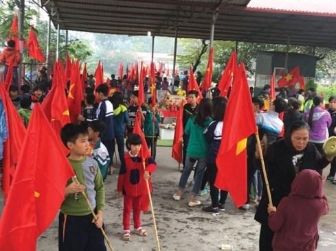 """Học sinh thay vì đến trường lại theo bố mẹ đi """"biểu tình"""" phản đối xây trung tâm thương mại. Ảnh: Báo Thanh Niên"""