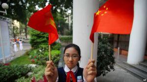 Học sinh Việt Nam cầm cờ Trung Quốc đón ông Tập Cận Bình (ảnh tư liệu). Photo: AP