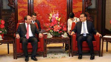 Báo trong nước xác nhận đơn thư tố cáo Phó thủ tướng Nguyễn Xuân Phúc (trái) là 'mạo danh'. Nguồn ảnh: xinhua.net