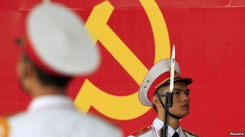 Binh lính quân đội đứng bảo vệ trước biểu tượng của Đảng Cộng sản Việt Nam trong buổi lễ kỷ niệm 85 năm thành lập Đảng tại Hà Nội ngày 2/2/2015. Ảnh: Reuters
