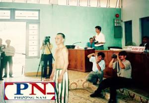 Ảnh: ông Huỳnh Văn Nén tại phiên tòa ngày 9/3/2005. Ông Nén cởi áo, chỉ những vết sẹo mà ông nói là do bị đánh. Nguồn: internet