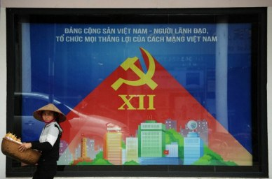 Một người bán hàng rong đi qua một tấm áp phích tuyên truyền cho Đại hội toàn quốc Đảng Cộng sản Việt Nam trên đường phố Hà Nội ngày 15 tháng 1 năm 2016. AFP Photo