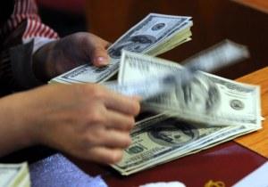 Một nhân viên ngân hàng tại Hà Nội đang kiểm tra tiền đô la Mỹ. Ảnh minh họa chụp trước đây. AFP PHOTO