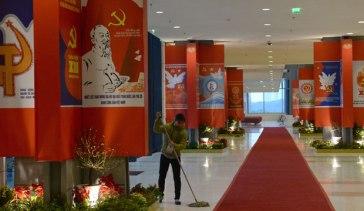 Một công nhân dọn dẹp hành lang dẫn đến phòng họp chính của Đại hội toàn quốc lần thứ 12 của Đảng Cộng sản Việt Nam được tổ chức tại Hà Nội vào ngày 26 tháng 1 năm 2016. Băng rôn mang cờ đảng treo khắp nơi. Ảnh: AFP.