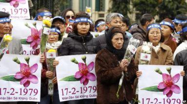 Người dân cầm biểu ngữ tại trung tâm Hà Nội để kỷ niệm 37 năm cuộc chiến biên giới Việt-Trung. Các cư dân đã thắp hương và đặt hoa tại tượng đài Lý Thái Tổ trong buổi lễ kéo dài khoảng một giờ đồng hồ. Ảnh: AP