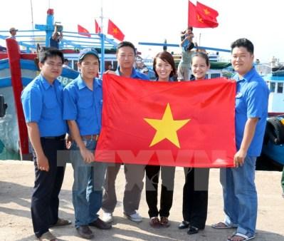 Các đoàn viên tự hào tặng cờ Tổ quốc cho ngư dân. (Ảnh: Nguyễn Thanh/TTXVN)