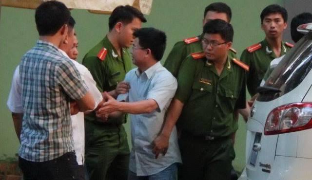 Ông Trần Minh Lợi (áo trắng) bị công an bắt chiều 22-3 - Ảnh: Trung Tân/ Tuổi Trẻ.