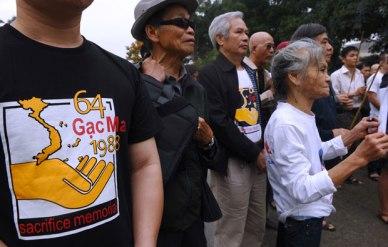 Những người biểu tình mặc áo thun với các áp phích ghi nhớ 64 thủy thủ Việt Nam thiệt mạng ngày 14 Tháng 3 năm 1988 trong trận Gạc Ma. Ảnh chụp hôm 14/3/2013 tại Hà Nội. AFP Photo