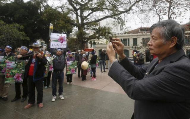 Ông Nguyễn Quang A đang chụp cảnh người biểu tình chống TQ ngày 17-2-2016. Ảnh: Reuters/ KHAM