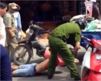 Anh Phạm Thiện Minh Phong, một thanh niên bán hàng rong ở Saigon bị công an nắm áo lôi đi.