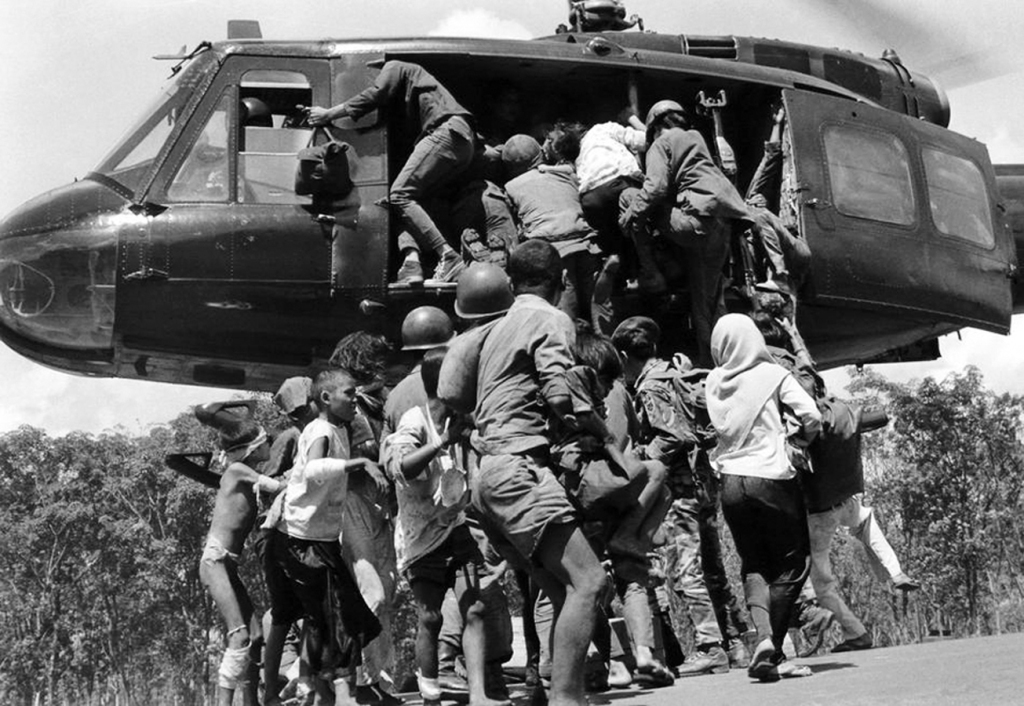 Lightly-wounded civilians and troops attempt to push their way aboard a South Vietnamese evacuation helicopter hovering over a stretch of Highway 13 near An Loc in Vietnam on June 25, 1972. (AP Photo)