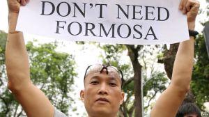 Người biểu tình cầm biểu ngữ phản đối công ty Formosa gây ô nhiễm dẫn tới vụ cá chết ở Hà Tĩnh. Ảnh: EPA