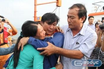 Thuyền trưởng Phạm Phú Thành (ở giữa) trong vòng tay người thân khi trở về đất liền. Ảnh: Hoàng Tuấn