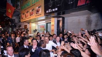 Tổng thống Obama bắt tay người dân sau khi thưởng thức món bún chả Hà Nội. Ảnh: EPA