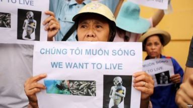 """Người dân xuống đường biểu tình phản đối vụ cá chết với biểu ngữ """"Chúng tôi muốn sống"""" tại Hà Nội, ngày 1/5/2016. Ảnh: EPA"""