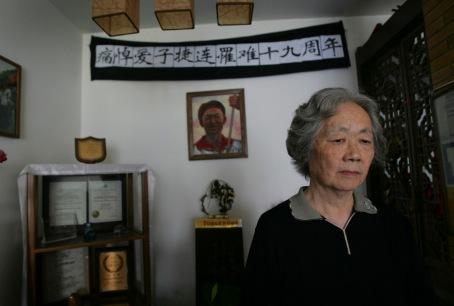 Ding Zilin, đồng sáng lập Phong trào các Bà Mẹ Thiên An Môn, đại diện cho các gia đình của những người đã chết trong năm 1989, qua vụ đàn áp của Bắc Kinh. Bà Zing đứng ở phía trước bàn thờ con trai Jiang Jielian, tại căn hộ của bà ở Bắc Kinh(AP Photo / Greg Baker)